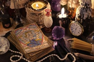 The tarot cards with crystal, black candles and magic objects.