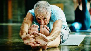 How to improve your flexibility: Image shows man stretching to reach his toes