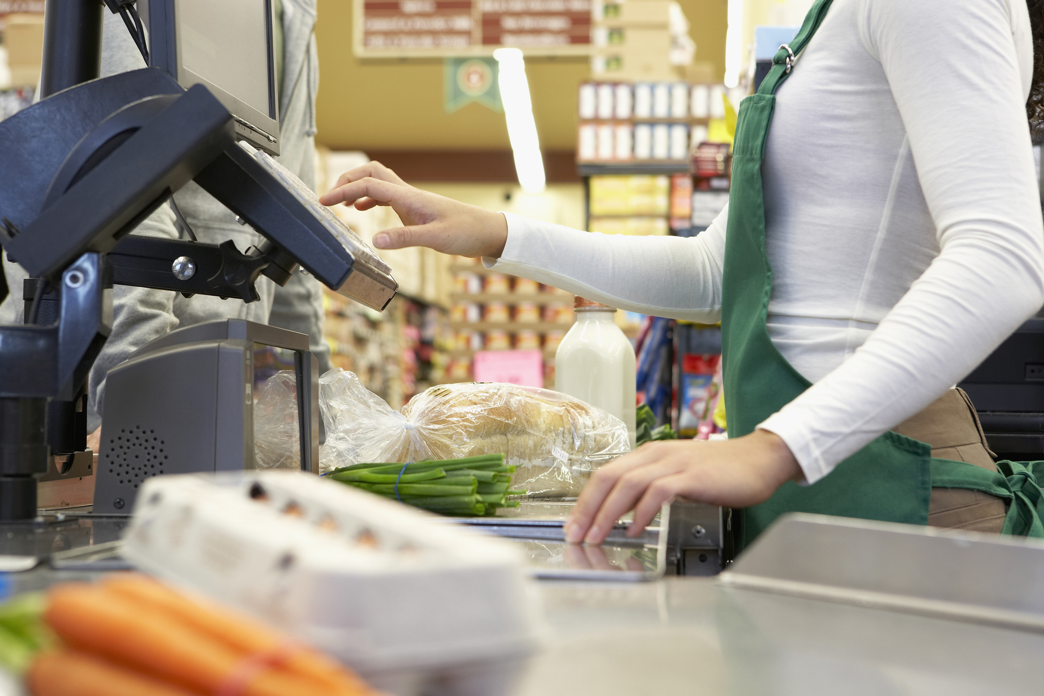 Cashier swiping groceries through a POS system