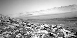 A photo of Mars taken by the Curiosity rover shows a bleak landscape of hills and hazy crater mountains.