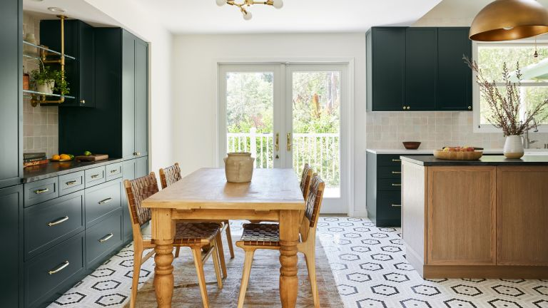A kitchen with a hexagonal mosaic floor, green cabinetry and rustic wooden dining table