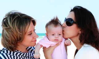 lesbian parents kissing baby