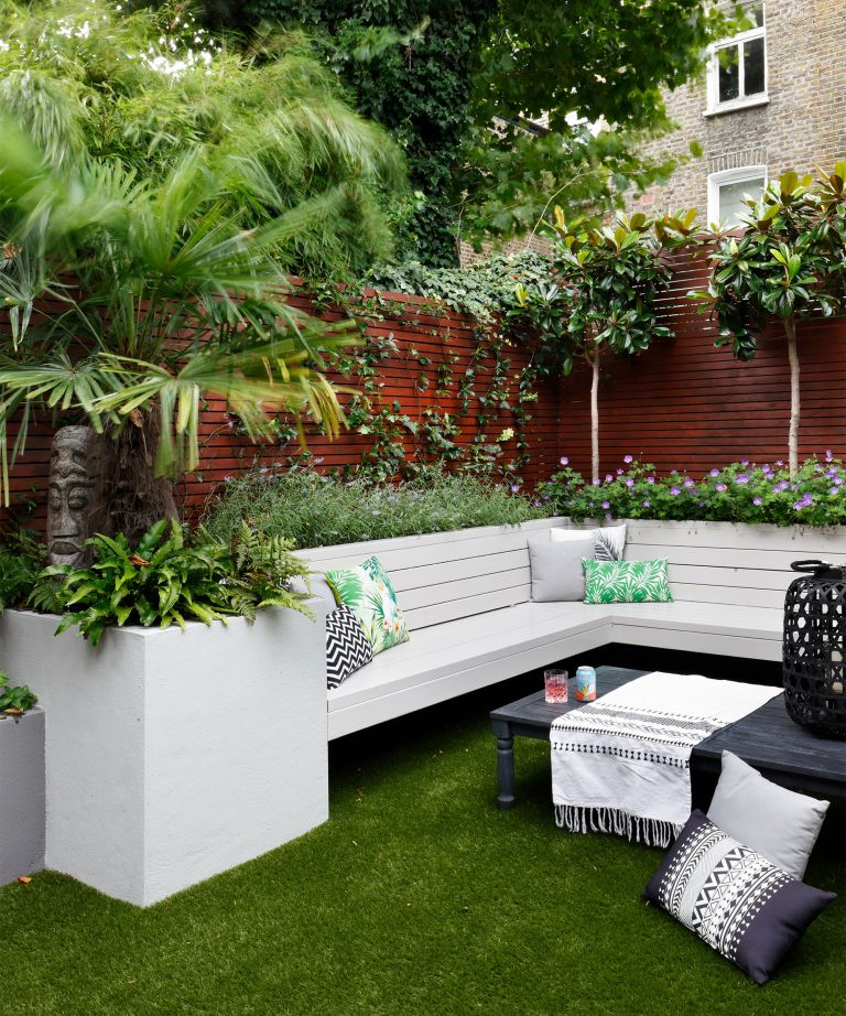 An example of the best trees for a small garden, with white L-shaped outdoor sofa.
