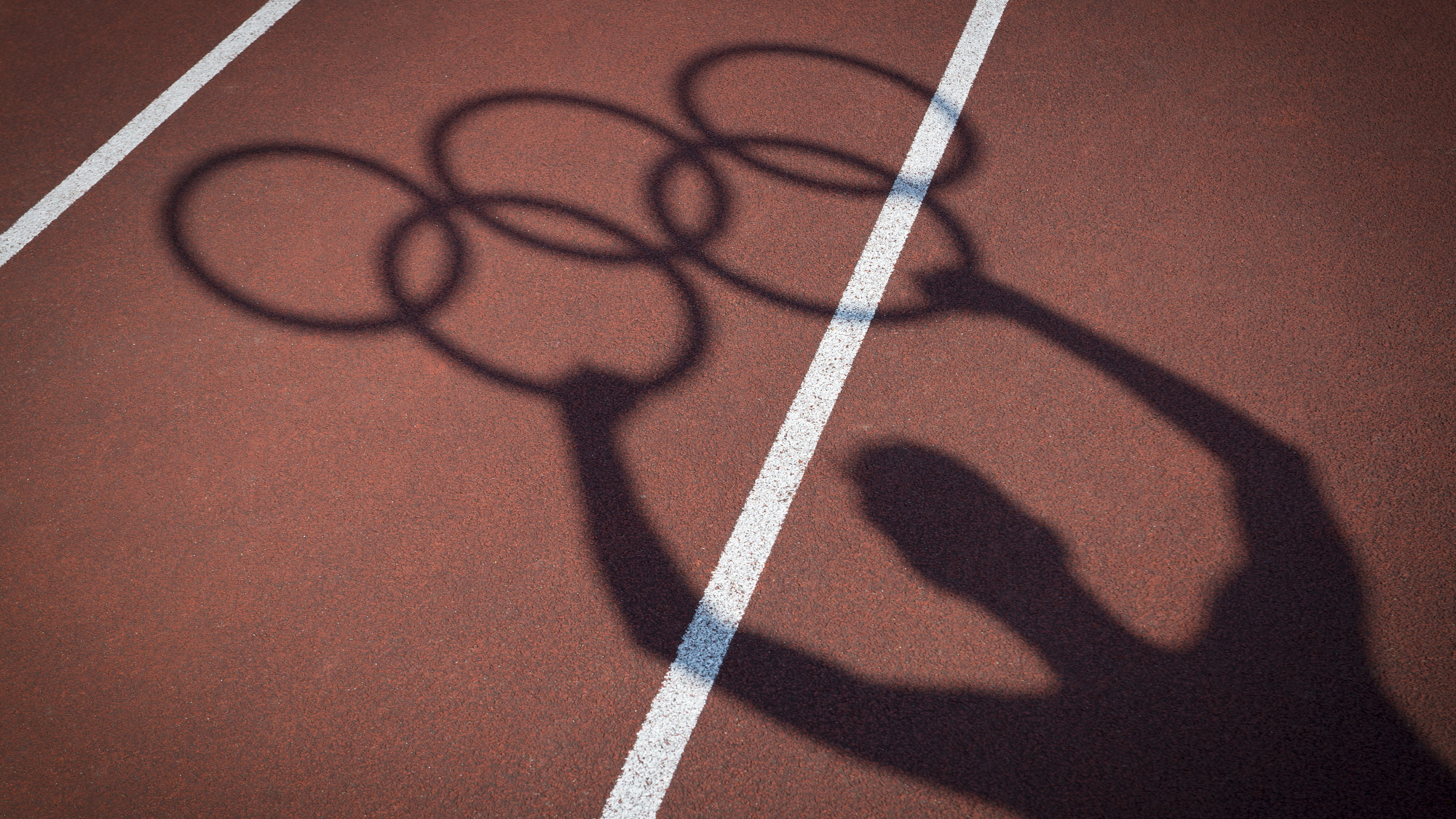 Shadow of man holding Olympic rings on athletics track