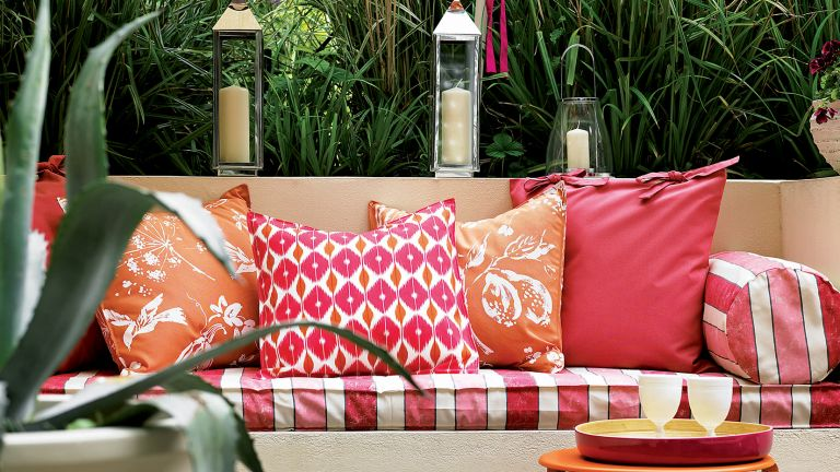 Simple garden ideas using terrace seating with red and orange cushions red and white striped fabric