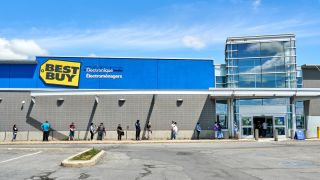 Line of people wearing masks waiting outside to enter Best Buy store in Montreal, Canada.