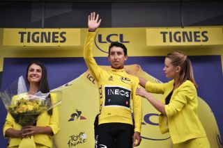 Egan Bernal (Team Ineos) is assisted with his yellow jersey after taking the race lead after stage 19 of the 2019 Tour de France in Tignes. In 2020, only one female hostess and one male host will take part in the Tour's podium protocol