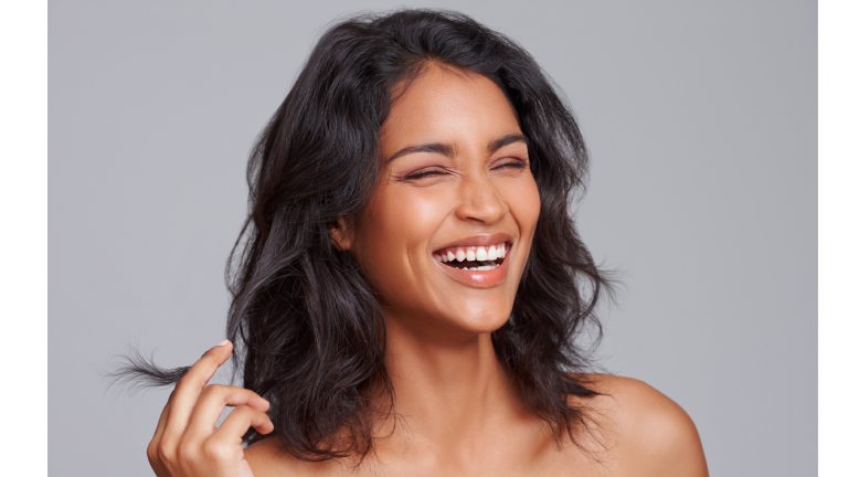 woman laughing and twirling her hair
