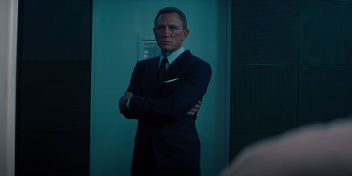 Daniel Craig dressed in a black suit with his arms folded in No Time To Die.