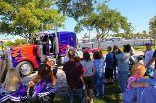 "NASA Kennedy Space Center employees and their families gather around 'Optimus Prime' in this snapshot taken during a photo opportunity Oct. 8, 2010 after the Transformer cars were used to film scenes of the new ""Transformers: The Dark of the Moon"" film at"