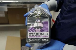 A Boeing technician holds a package of CST-100 Starliner Orbital Flight Test-2 patches to be flown on board the mission.