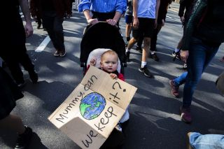 A baby clutches a sign during a climate strike rally on Sept. 20, 2019, in Sydney, Australia, part of a global mass day of action on the climate crisis.