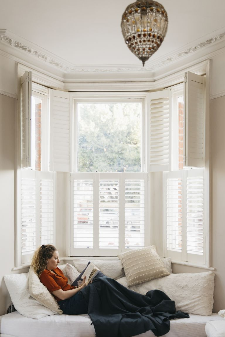 White wooden bay window with woman reading on seating space with cushions