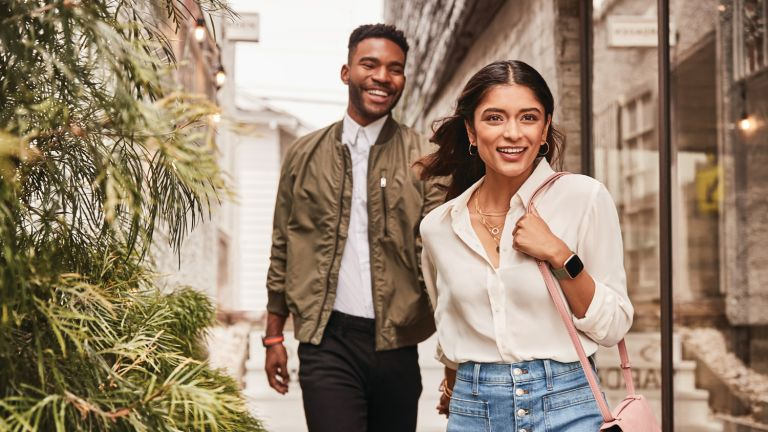 A woman and a man walking down the street, both wearing the best cheap smartwatch