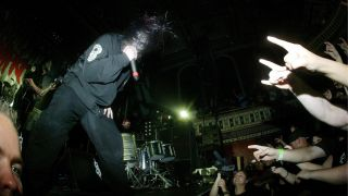 Mick Thomson (L) Corey Taylor performing on stage, audience hands, video camera