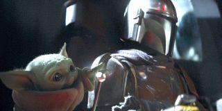 Baby Yoda The Child reaches out next to The Mandalorian Season 1