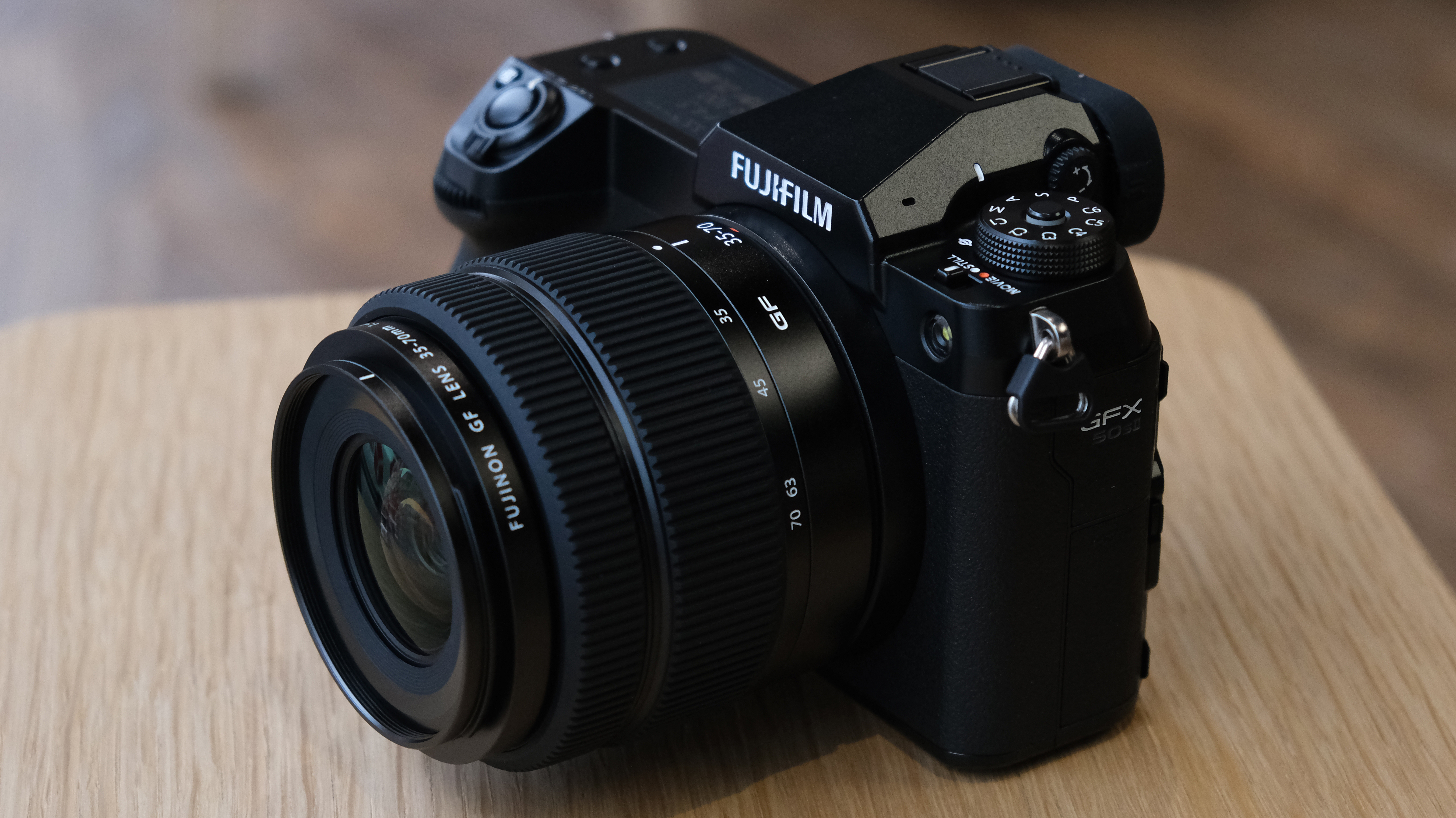 The Fujifilm GFX50S II on a wooden table