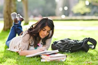 A woman studies on the lawn of a college campus.