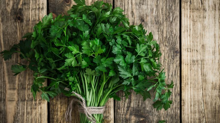 bunch of parsley on a wooden chopping board