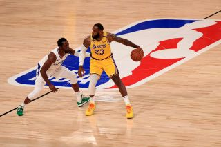 LeBron James #23 of the Los Angeles Lakers dribbles the ball against Reggie Jackson #1 of the LA Clippers of the game at The Arena at ESPN Wide World Of Sports Complex on July 30, 2020 in Lake Buena Vista, Florida.