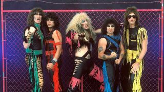 Twisted Sister in front of a pink fence