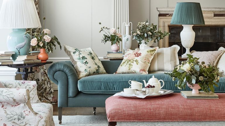 A living room with turquoise velvet sofa, pink upholstered footstool and floral white cushions