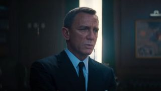 Daniel Craig stands with a look of concern in No Time To Die.