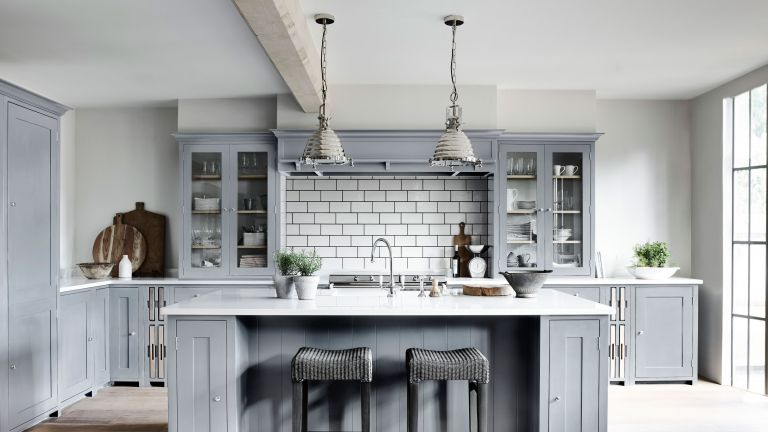 pale blue kitchen with island and white tiles