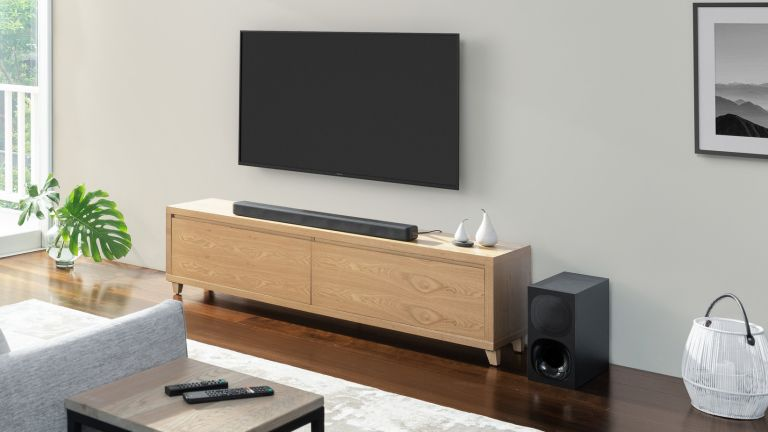 Best soundbar 2020, living room with a black Sony soundbar sitting on a wooden TV bench, with TV wall mounted above, and subwoofer on the floor to the side