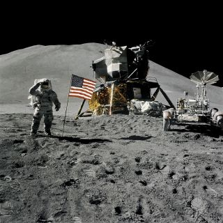 Astronaut James B. Irwin, lunar module pilot, during the Apollo 15 lunar surface extravehicular activity (EVA) on August 1, 1971, at the Hadley-Apennine landing site. The first Lunar Roving Vehicle (LRV) on the moon, stands to the right.