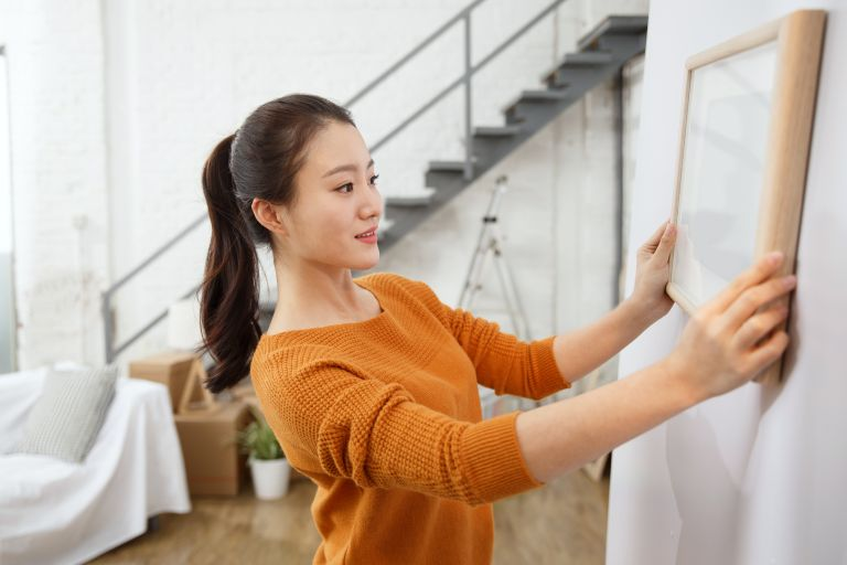 woman hanging pictures on wall