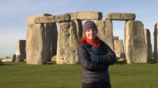 Professor Alice Roberts stands in front of Stonehenge