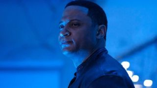 Diggle smiling in a room with blue light Supergirl CW