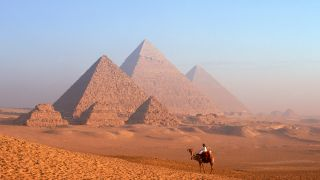 A Bedouin man on a camel by the Pyramids of Khafre and Menkaure at the Giza Necropolis in Egypt.