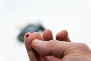A man pricks his finger to measure his blood sugar level.