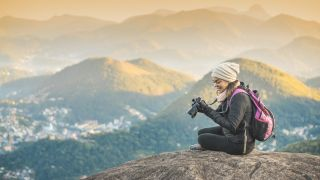 Best cameras for hiking - woman sitting on mountain looking at her Sony camera