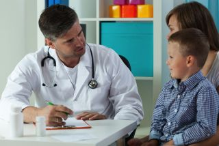 A boy talks with his doctor.