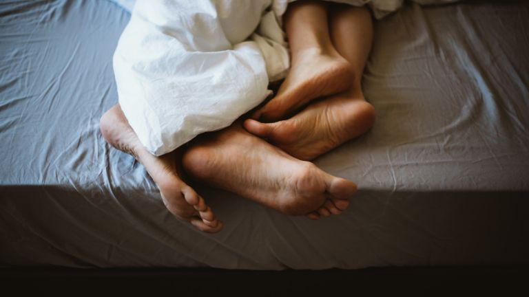Feet of a couple in bed - stock photo for sex therapy app Lover