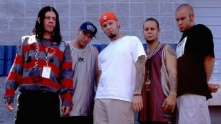 Limp Bizkit standing in a row in front of a wall