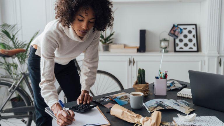 Freelancer standing at hert desk, using calculator, taking notes