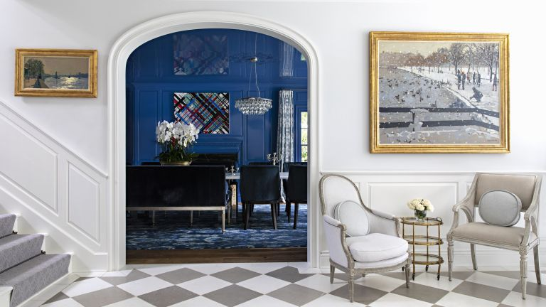 A white entrance hall with grey and white checkered floor and entrance to blue dining room