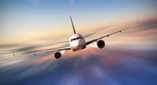 Commercial airplane flying above clouds in dramatic sunset light, blur motion.