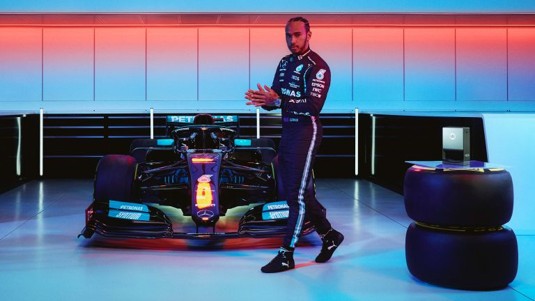 Lewis Hamilton posed next to his racing car, with INEOS Hand Sanitizer dispenser
