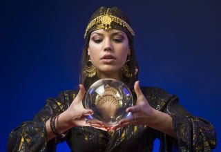 A fortune-teller holds a crystal ball.