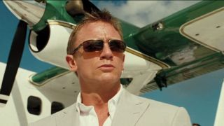 Daniel Craig wearing sunglasses in front of a plane in Casino Royale.