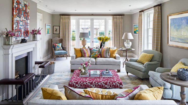 Beige living room ideas with neutral sofas and colorful yellow and pink accents in the cushions, drapes, ottoman and wall art.