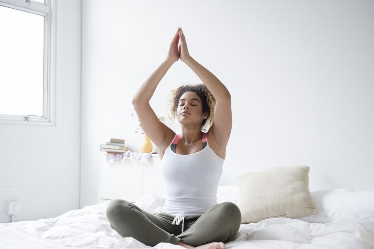 Mixed Race woman sitting on bed meditating and doing yoga