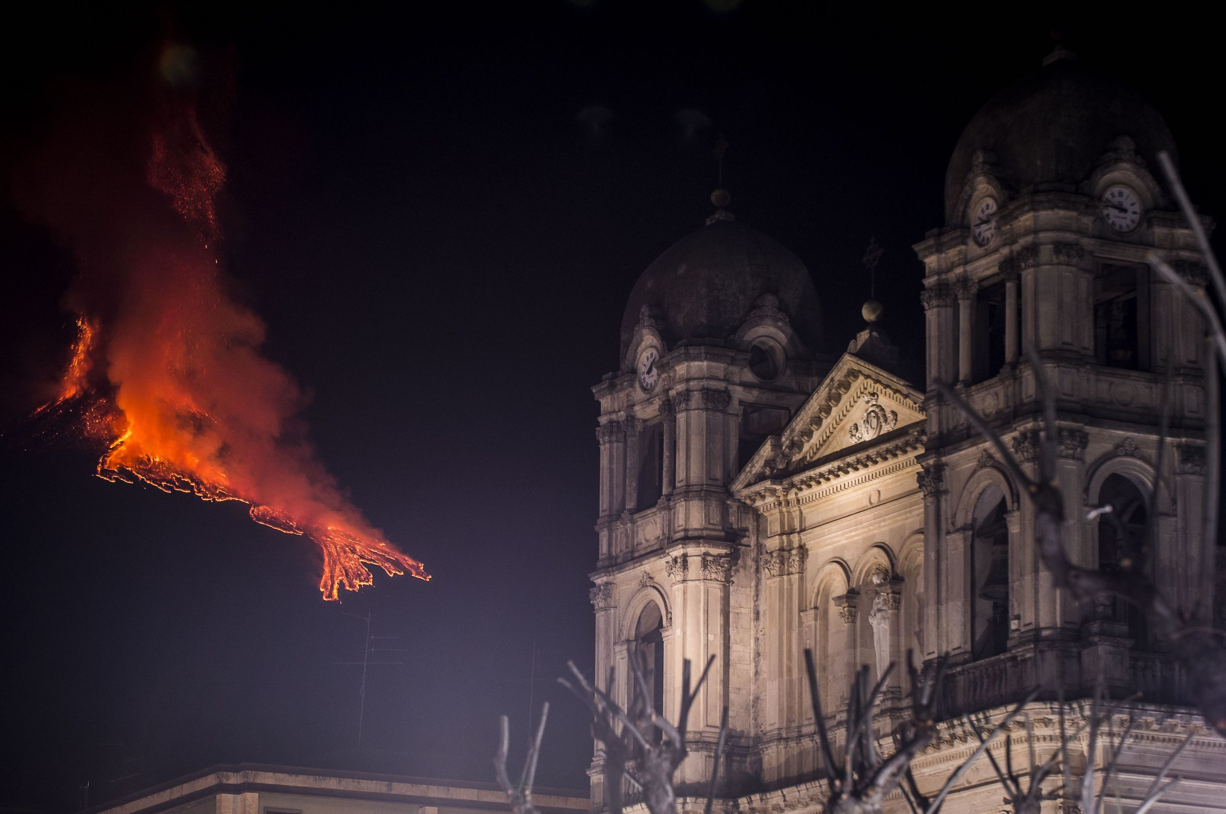 A church in Catania, Italy stands undisturbed as Mount Etna erupts miles away.
