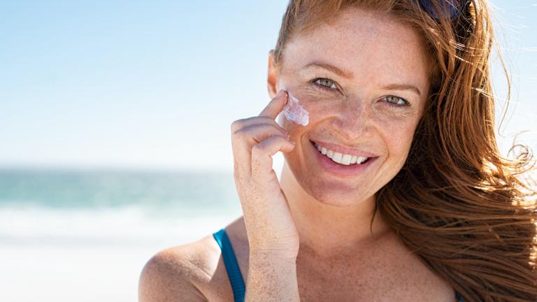 Redhead woman applying sunscreen on a beach