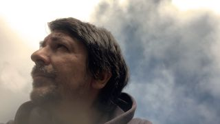 Sel Balamir June 2021 portrait against a sky